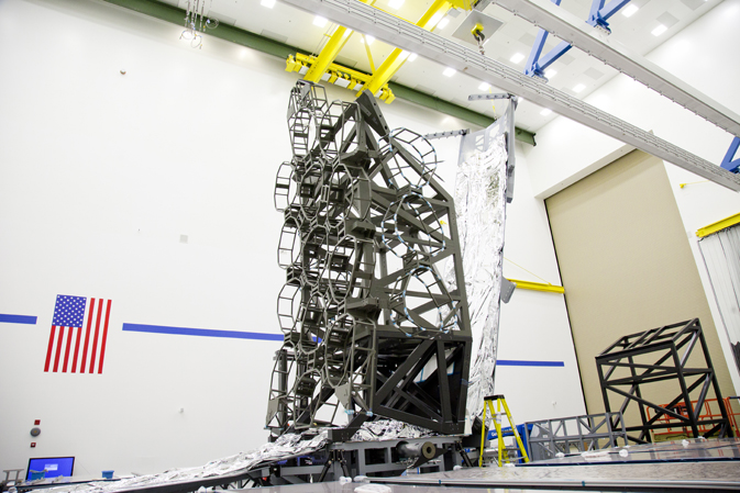 Central honeycomb scaffolding sits atop the folded silvery foil sunshield, which is partially deployed, in a cleanroom