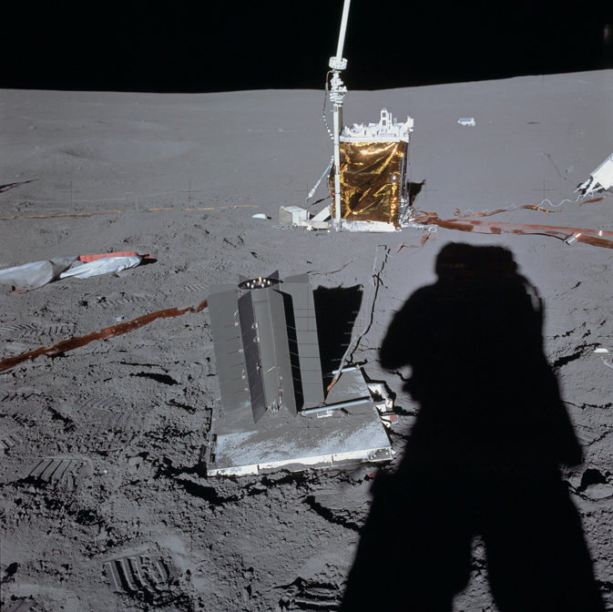 shadow of Apollo 14 astronaut looms over footprints, packages of instruments and wiring across the lunar surface