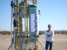 Kyle Nyberg of Masten observes the Xombie vehicle on the pad prior to flight test operations.