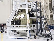 Technicians lower a special fixture around an Orion spacecraft inside the high bay of the Operations & Checkout Building at NASA's Kennedy Space Center in Florida. Photo credit: NASA/Tim Jacobs