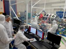 Engineers in clean suits perform tests on the LADEE spacecraft.