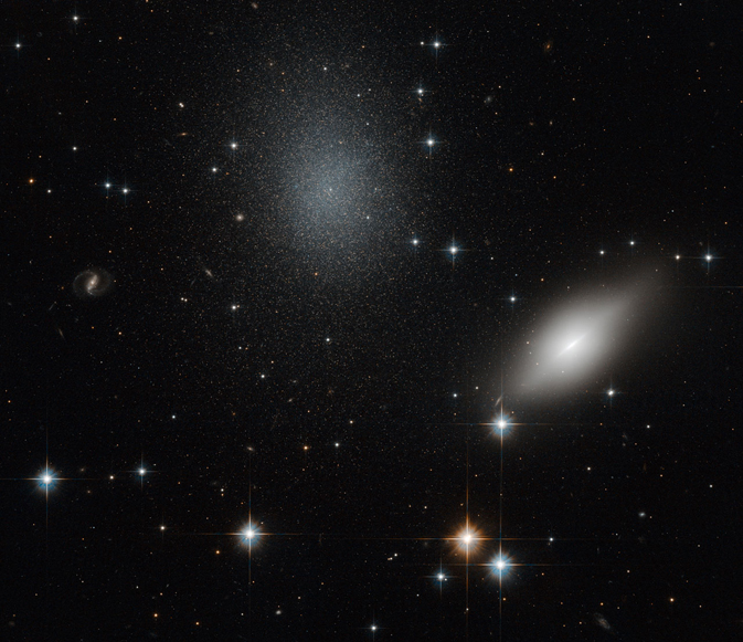 Background stars burn from behind an almond-shaped blurry white galaxy and a diffuse speckled glob of stars