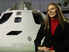 Amber Gell sitting in front of Orion capsule
