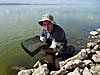 Mike Lee standing in shallow water near a rocky shore holding a salt pond microbial mat