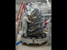 Spacecraft technicians in a clean room at NASA's Ames Research Center, Moffett Field, Calif., install protective bags around NASA's LADEE observatory before it is sealed in the shipping container.