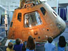 A group of children look at an Apollo capsule exhibit in a museum