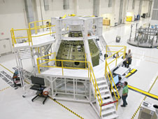 A birdcage tool along with work platforms surround the Orion Exploration Flight Test 1 crew module.