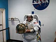 A college student wearing a white EMU suit holds a helmet, with the NASA logo in the background