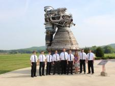 Engineers dressed in Apollo style white shirts with black ties stand by a Saturn V F1 engine.