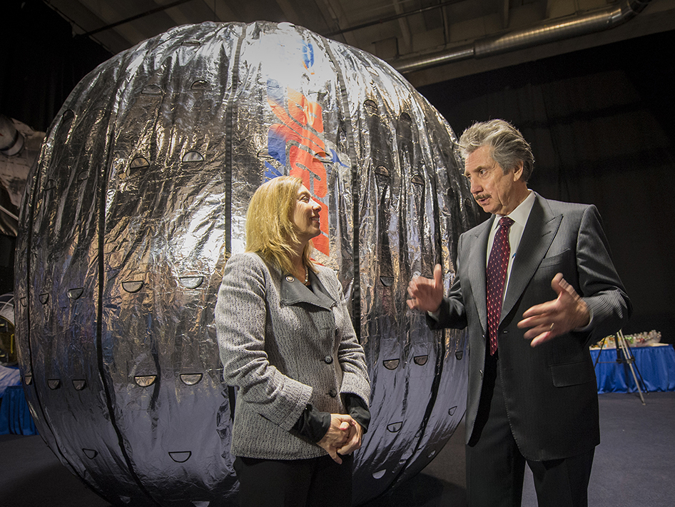 NASA Deputy Administrator Lori Garver and President and founder of Bigelow Aerospace, Robert T. Bigelow, talk while standing next to the Bigelow Expandable Activity Module (BEAM). Photo Credit: NASA/Bill Ingalls