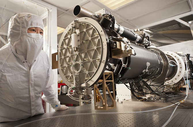 An Engineer inspects the integrated IRIS solar telescope.