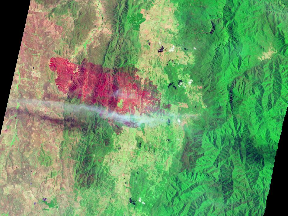 a large red fire scar cuts across swaths of tan and green, overlayed by a thin stream of clouds blowing left to right