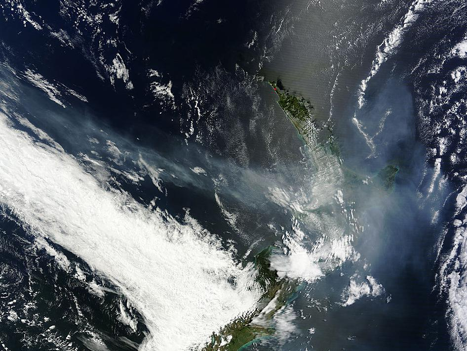 A light brown haze washes over New Zealand, contrasted with stark-white clouds and blue-black sea with sun glints.