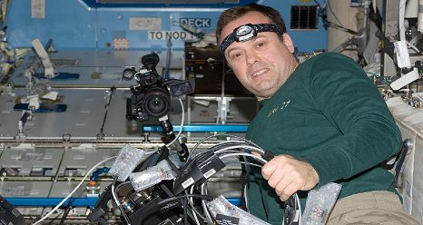 NASA astronaut Ron Garan, Expedition 27 flight engineer, works with ISS Agricultural Camera (ISSAC) hardware in the Destiny laboratory of the International Space Station. ISSAC, a successor of the earlier AgCam, will operate in conjunction with EarthKAM, both instruments to conduct simultaneous but independent operations in the WORF rack in Destiny. (NASA)