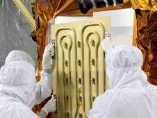 Technicians work on the LDCM spacecraft.