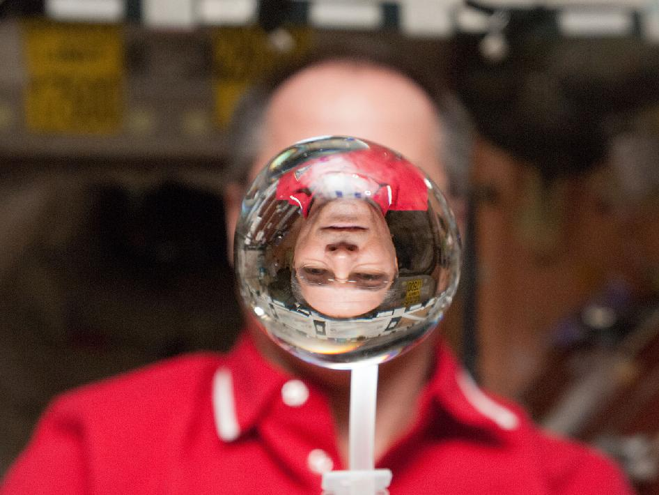 NASA astronaut Kevin Ford, Expedition 34 commander, watches a water bubble float freely between him and the camera, showing his image refracted, in the Unity node of the International Space Station. Image Credit: NASA