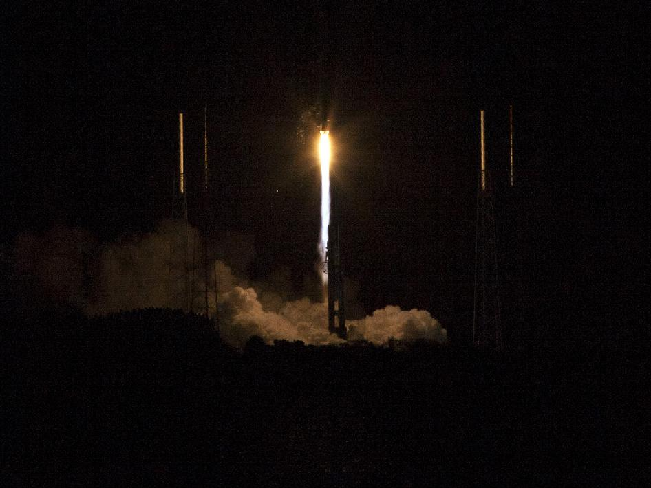 The Atlas V rocket lifts off the launch pad into a dark night sky.