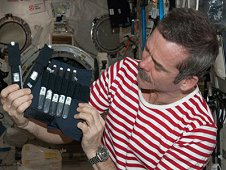 Canadian Space Agency astronaut Chris Hadfield holds bubble detectors for the RaDI-N 2 investigation in the International Space Station's Kibo laboratory. This investigation measures neutron radiation levels onboard the space station. It uses bubble detectors as neutron monitors which have been designed to only detect neutrons and ignore all other radiation. (NASA)