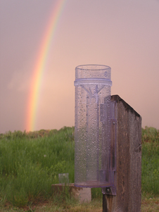 rain gauge with rainbow in background