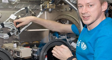Astronaut Frank DeWinne works with the Selectable Optical Diagnostics Instrument Influence of Vibration on Diffusion in Liquids (SODI-IVIDIL) hardware in the Microgravity Science Glovebox (MSG) aboard the International Space Station. (Credit NASA)