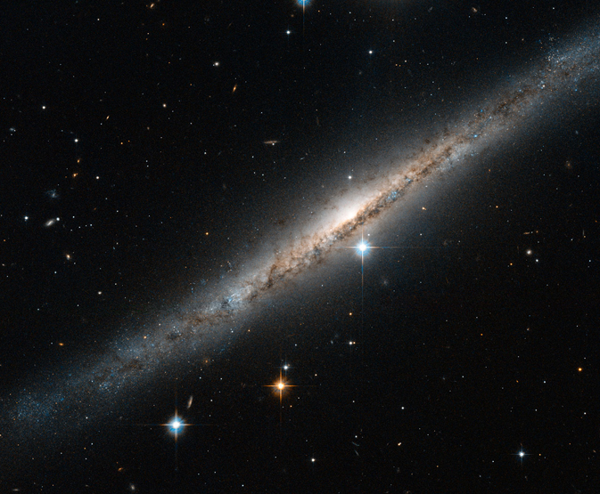 A bend sinister of a side-on galaxy, showing a central dark dust lane and several bright stars shining through