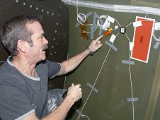 Canadian Space Agency astronaut Chris Hadfield installs Ultrasonic Background Noise Tests (UBNT) sensors behind a rack in Destiny, using the space station as Testbed for Analog Research (ISTAR) procedures. These sensors detect high-frequency noise levels generated by station hardware and equipment operating within Destiny. (NASA)