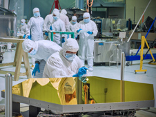 Technicians and scientists check out one of the Webb telescope's flight mirrors in the clean room at Goddard Space Flight Center.