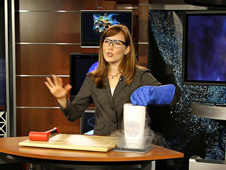 NASA Astrophysicist Amber Straughn emonstrates the cold environment where the Webb telescope will be by dipping flexible rubber surgical tubing into liquid nitrogen in a demonstration video.