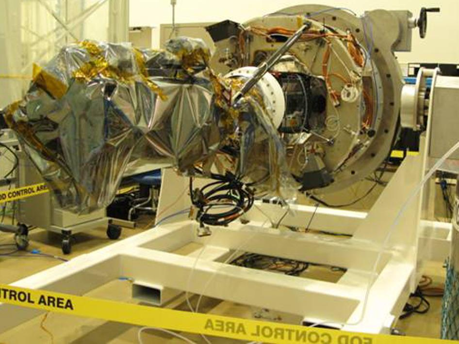 The IRIS telescope, wrapped in a protective film, is mated to the spacecraft deck.