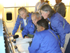 Airborne Astronomy Ambassadors (from left) Constance Gartner, Vince Washington, Ira Hardin and Chelen Johnson at the educators' work station aboard the SOFIA observatory during a flight on the night of Feb. 12-13, 2013.