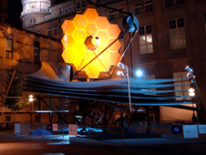 JWST's golden mirrors lit up, full-scale outside a building. It's only a model