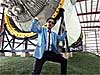 A man wearing sunglasses and a blue suit and tie dances in front of a rocket