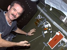 Canadian Space Agency astronaut Chris Hadfield, Expedition 34 Flight Engineer, installing Ultra-Sonic Background Noise Test sensors behind a rack in the Destiny laboratory of the International Space Station. These sensors detect high frequency noise levels generated by station hardware and equipment. (NASA)