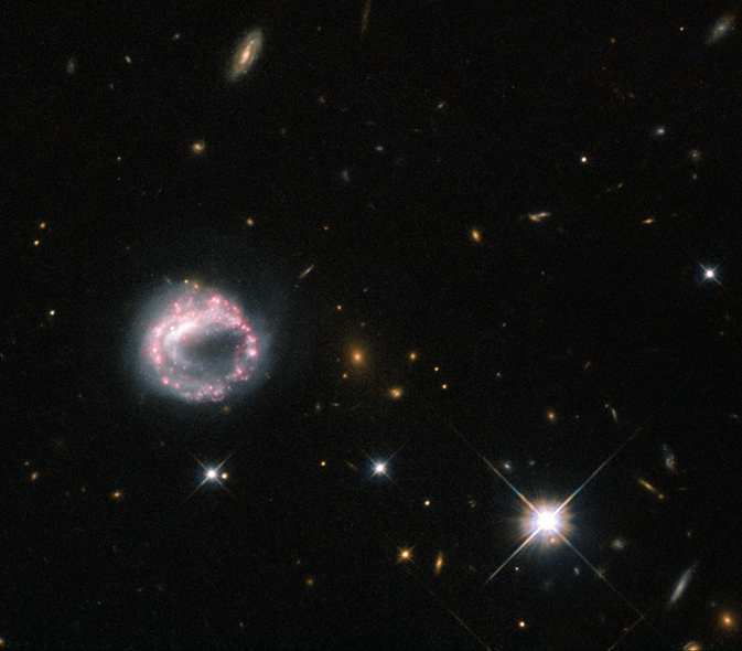 A white circular structure ringed with pink clusters of old stars, a bright star to the right and various distant galaxies
