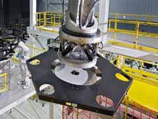 The robot arm moves the surrogate mirror segment to the test backplane for placement.  Credit: NASA/Chris Gunn