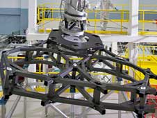 A surrogate mirror segment  is being carefully attached to the a test structure that will hold 18 of those mirrors on the Webb telescope.