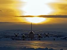The P-3 is waiting outside the hangar at Thule Air Base with the Greenland Ice sheet in the background.