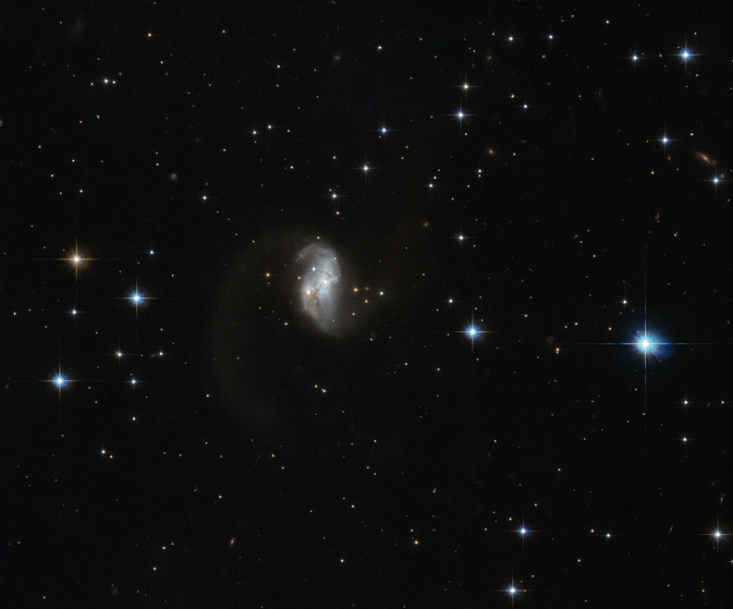 The central portion of this spiral galaxy is the only part visible, giving it an asymmetric form with a tail