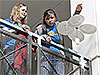 Two students release their entry in the Science Olympiad's 'Rotor Egg Drop' competition from the second story of a building