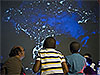 Children gaze at an inflatable planetarium