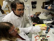 Dr. Howard Levine, chief scientist in NASA's International Space Station Ground Processing and Research Directorate, watches as Michele Koralewicz of QinetiQ North America assembles a Biological Research in Canisters (BRIC) experiment package. (NASA)