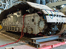 Technicians in the Vehicle Assembly Building are jacking crawler-transporter-2 four feet off the floor to facilitate removal of the roller bearing assemblies.