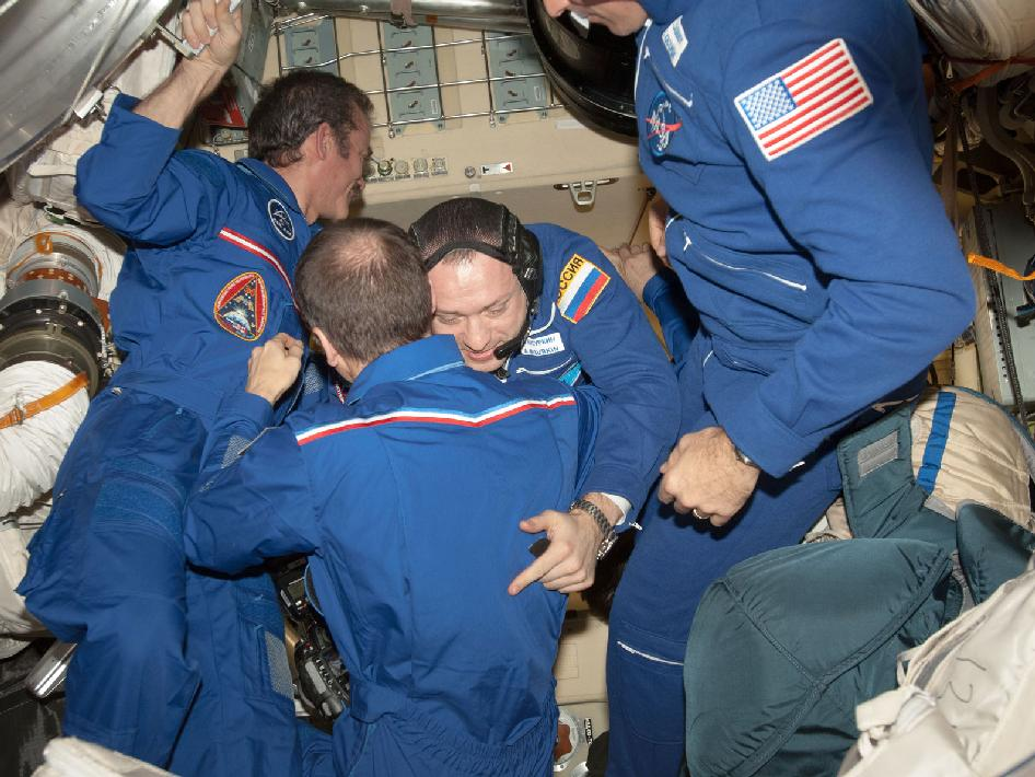 Expedition 35 crew members greet one another