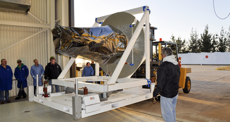 Workers unload NASA's IRIS spacecraft from a truck at the processing facility at Vandenberg where the spacecraft will be readied for launch aboard an Orbital Sciences Pegasus XL rocket
