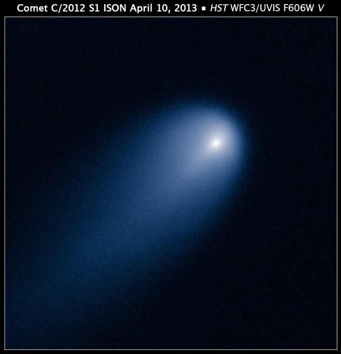 A blue-white comet burns through the blackness, tail blazing southwest of a bright point of white light