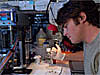Intern Dennis Murray works on a lab-on-a-chip prototype in a laboratory