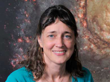 portrait of a woman smiling in front of a Hubble galaxy image. a hubble model on a desk next to her elbow