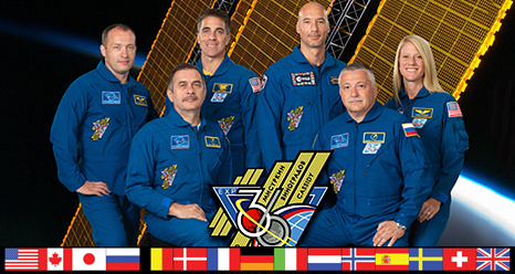 The Expedition 36 crew poses in front of a picture of the space station's solar panels