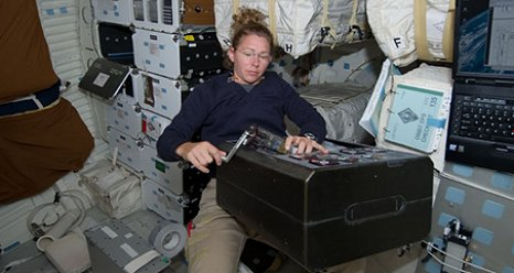 Mission specialist Sandra Magnus works with a Group Activation Pack (GAP) for the Recombinant Attenuated Salmonella Vaccine (RASV) experiment. (NASA).