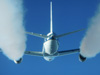 Puffy white exhaust contrails stream from the engines of NASA's DC-8 flying laboratory in this photo taken from an HU-25 Falcon flying in trail about 300 feet behind.